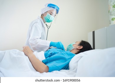 Doctor wearing PPE suit and Surgical mask and Checking infected patient in quarantine room Covid-19 (Coronavirus)Coronavirus outbreak or Covid-19, Concept of Covid-19 quarantine