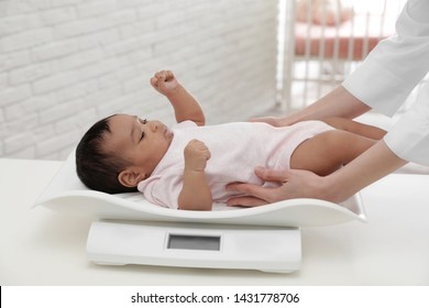 Doctor weighting African-American baby on scales in light room