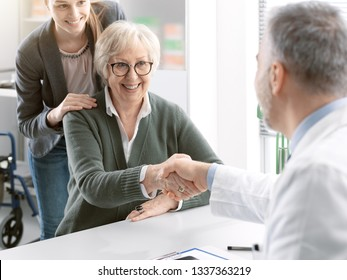 Doctor welcoming a smiling senior female patient in his office and shaking her hand