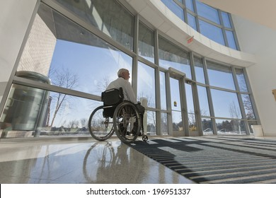 Doctor in a wheelchair at an accessible hospital entrance