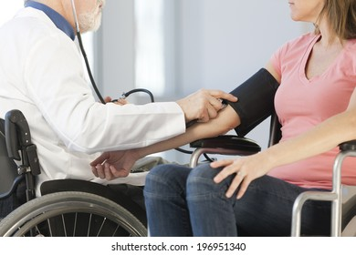 Doctor in a wheelchair taking the blood pressure of a female patient