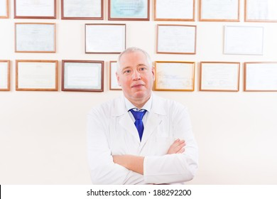 doctor white coat, folded hands over office wall with certificate background