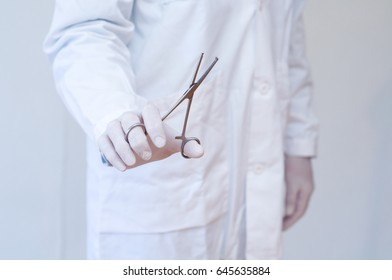 Doctor in white coat with hand caliper, without showing his face
