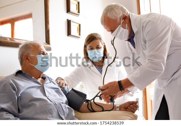 médico con una bata blanca toma la presión de un paciente anciano con una máscara, sentado al lado de un médico que le asiste