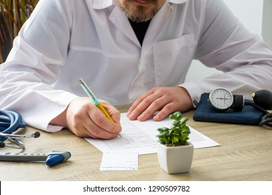Doctor in white coat at workplace in hospital office seeing patients and fills medical documentations history of disease with focus on hand of physician. Scene with daily work of doctors with patients