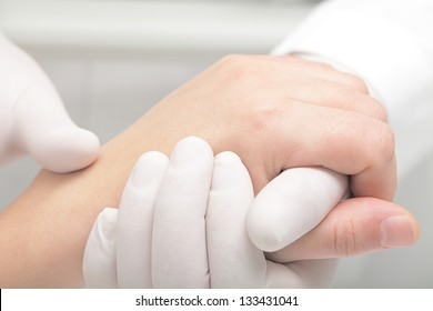 Doctor in white gloves gently holds the patient's arm