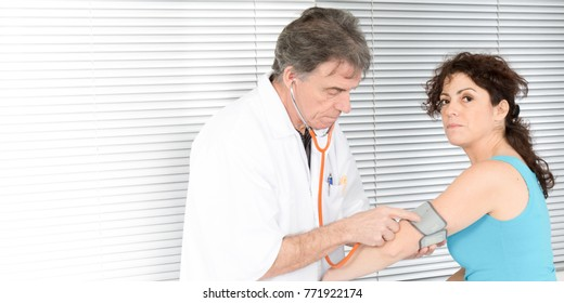 doctor with white hair measures the blood pressure of his female patient tension client