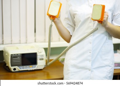 Doctor in white holds electroshock probes in hospital cabinet, noface
