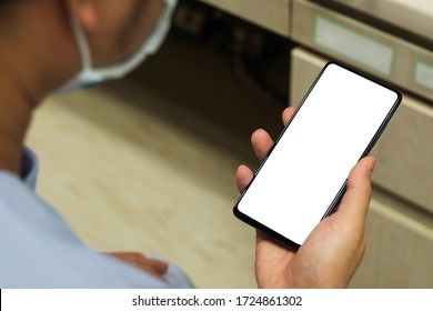A doctor And white screen smartphone placed near a stethoscope in a hospital