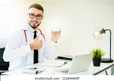 Doctor Who holds a medicine box. Sitting on a desk in the Clinic Recommended to use properly. To provide correct treatment for patients. There are no side effects. Concept Medical Business Hospital