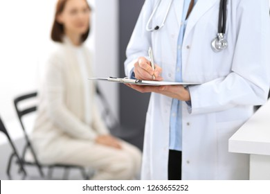 Doctor woman filling up medical form while standing near reception desk at clinic or emergency hospital.Unknown physician at work, hands close-up. Medicine and patient service concept