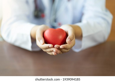 Doctor woman holding red heart toy. love concept