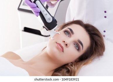 Doctor woman making to patient laser skin resurfacing in aesthetic medicine.
