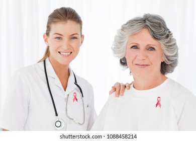 Doctor woman and patient with breast cancer awareness ribbons