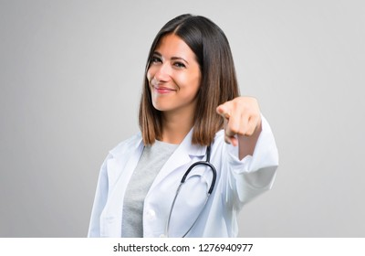 Doctor woman with stethoscope points finger at you with a confident expression on grey background
