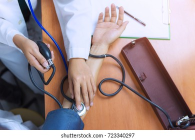 Doctor women is checking patient with stethoscope and measure blood pressure. / top view