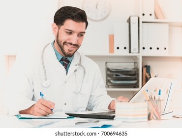 Doctor is working with documents in laptop in his work place.