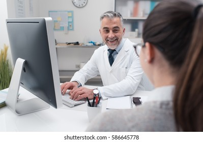 Doctor working with his computer in the office, he is visiting a patient and typing on a keyboard