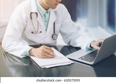 Doctor working with laptop computer and writing on paperwork in the hospital.
