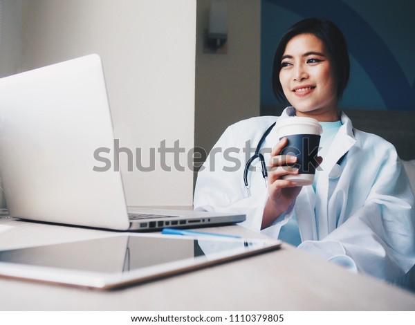 Doctor working with laptop at her office.