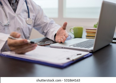Doctor working for medical Exam, Healthcare and medically concept,Stethoscope with clipboard and Laptop ,coffee cup on desk.hand of specialist on a prescription,test results  background,vintage color