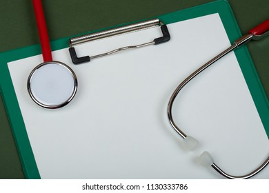 Doctor workplace - red stethoscope and empty clipboard on green paper background