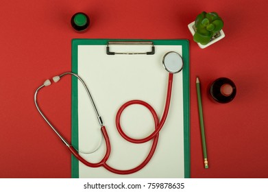 Doctor workplace - red stethoscope, medical bottles and empty green clipboard on red paper background