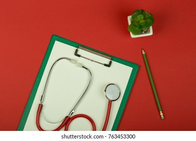 Doctor workplace - red stethoscope, pencil and empty green clipboard on red paper background