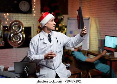 The doctor works on New Year's Eve. He carefully examines the X-ray. Against the background sits his colleague and works at the computer.