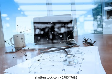 Doctor workspace with laptop computer in medical workspace office and medical network media diagram as concept