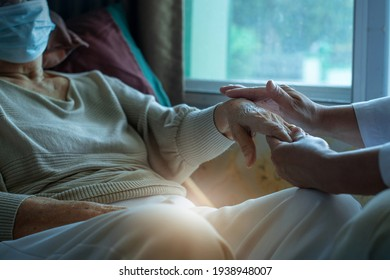 Doctor worriedly and holding the senior woman's hand, elderly wearing medical mask, general practitioner visiting her at home, elderly health care concept, selective focus