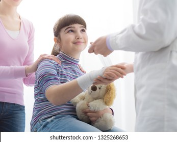Doctor wrapping a girl's injured wrist with gauze and bandage, the mother is standing next to the daughter, first aid and healthcare concept