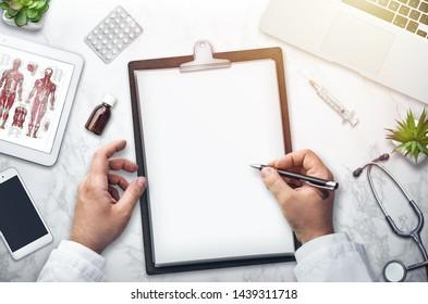 Docteur écrivant sur le bureau, vue de dessus, arrière-plan