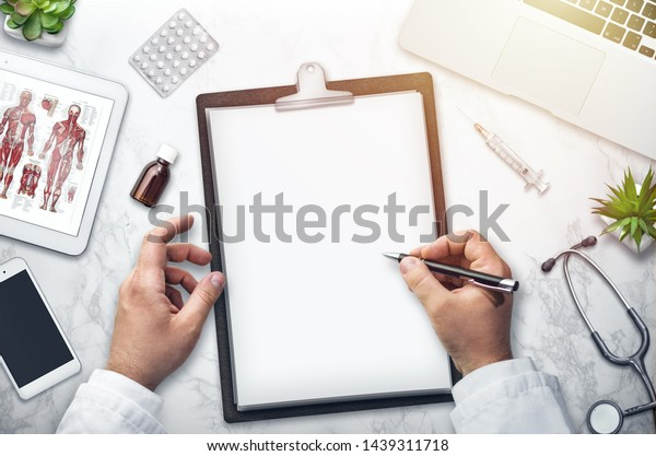 Doctor writing on the desk, top view, background