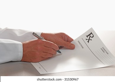Doctor writing out prescription on RX form white background