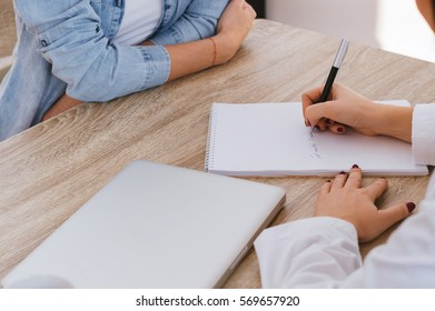 Doctor writing a prescription to a female patient