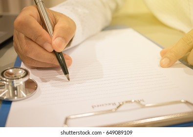 doctor is writing a prescription and have stethoscope with record information paper and Laptop, Healthcare and medical concept