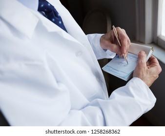 A doctor writing a prescription on a blue prescription pad.