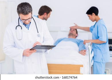 Doctor writing reports with patient and surgeon in background at the hospital