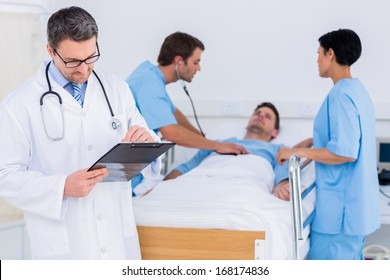 Doctor writing reports with patient and surgeons in background at the hospital