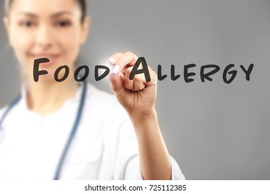 Doctor writing text FOOD ALLERGY on virtual screen against grey background