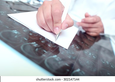 Doctor wrote on a paper examining the tomography scan of the patient