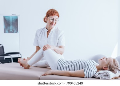 Doctor and young girl during physiotherapy massage in a white office