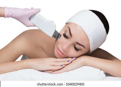 The doctor-cosmetologist makes the apparatus a procedure of ultrasound cleaning of the facial skin of a beautiful young woman in a beauty salon. Cosmetology and professional skin care.