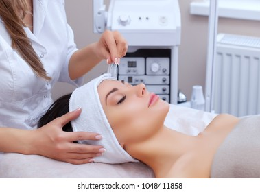 The doctor-cosmetologist makes the face vacuum therapy on the cheek of a beautiful, young woman in a beauty salon.Cosmetology and professional skin care.