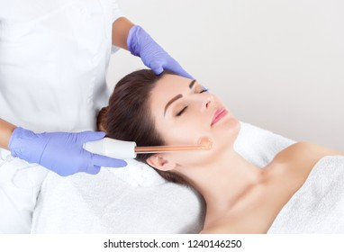 The doctor-cosmetologist makes the Microcurrent therapy procedure of a beautiful, young woman in a beauty salon.Cosmetology and professional skin care.