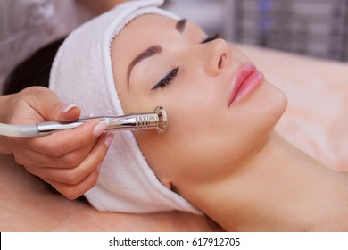 The doctor-cosmetologist makes the procedure Microdermabrasion of the facial skin of a beautiful, young woman in a beauty salon.Cosmetology and professional skin care.