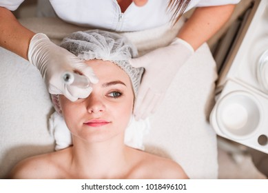 The doctor-cosmetologist makes a procedure of ultrasound facial cleaning of the skin of a beautiful, young woman in a beauty salon, spa. Cosmetology and professional skin care.