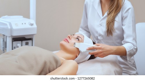 The doctor-cosmetologist makes the ultrasound cleaning procedure of the facial skin of a beautiful, young woman in a beauty salon. Cosmetology and professional skin care.