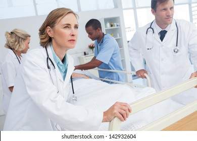 Doctors about to walk with patient bed in an emergency